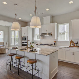Transitional eat-in kitchen photos - Transitional l-shaped medium tone wood floor and brown floor eat-in kitchen photo in Charleston with an undermount sink, shaker cabinets, white cabinets, white backsplash, subway tile backsplash, stainless steel appliances, an island and gray countertops