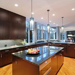 シカゴの大きいコンテンポラリースタイルのおしゃれなキッチン (アンダーカウンターシンク、フラットパネル扉のキャビネット、濃色木目調キャビネット、コンクリートカウンター、グレーのキッチンパネル、ボーダータイルのキッチンパネル、シルバーの調理設備、無垢フローリング、茶色い床) の写真