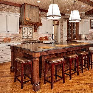 Imagen de cocina rústica con fregadero bajoencimera, armarios con paneles empotrados, puertas de armario beige, salpicadero de ladrillos, electrodomésticos de acero inoxidable, suelo de madera en tonos medios, una isla y encimeras beige
