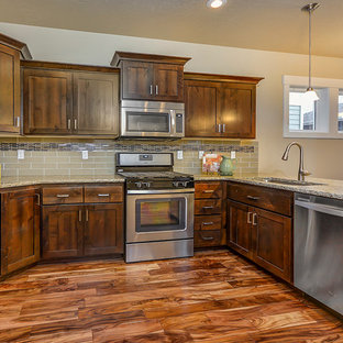 Traditional open concept kitchen pictures - Elegant u-shaped medium tone wood floor open concept kitchen photo in Boise with an undermount sink, shaker cabinets, medium tone wood cabinets, brown backsplash, stainless steel appliances and a peninsula