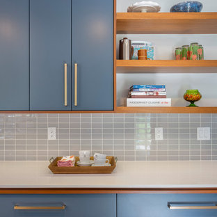 Mid-sized midcentury galley eat-in kitchen in Kansas City with an undermount sink, flat-panel cabinets, blue cabinets, quartz benchtops, grey splashback, porcelain splashback, stainless steel appliances, concrete floors, with island and grey floor.