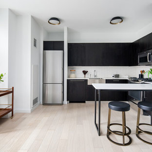 Contemporary kitchen designs - Kitchen - contemporary l-shaped light wood floor and beige floor kitchen idea in New York with a farmhouse sink, flat-panel cabinets, black cabinets, white backsplash, subway tile backsplash, stainless steel appliances and a peninsula