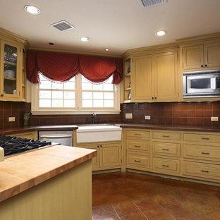 Mittelgroße Klassische Wohnküche in U-Form mit Kassettenfronten, beigen Schränken, Küchenrückwand in Braun, Rückwand aus Porzellanfliesen, Küchengeräten aus Edelstahl, Porzellan-Bodenfliesen, braunem Boden, Kupfer-Arbeitsplatte und oranger Arbeitsplatte in Houston