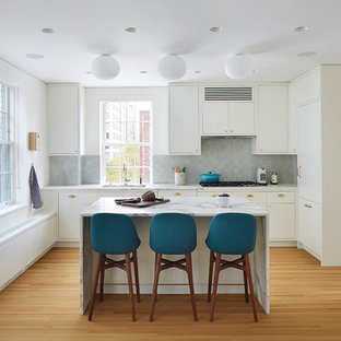Mid-sized trendy l-shaped light wood floor eat-in kitchen photo in New York with an undermount sink, flat-panel cabinets, white cabinets, gray backsplash, an island, marble countertops, ceramic backsplash and paneled appliances