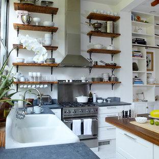 Offene, Mittelgroße Maritime Küche in U-Form mit Landhausspüle, offenen Schränken, weißen Schränken, Arbeitsplatte aus Holz, Küchengeräten aus Edelstahl, gebeiztem Holzboden, Kücheninsel, weißem Boden und grauer Arbeitsplatte in New York