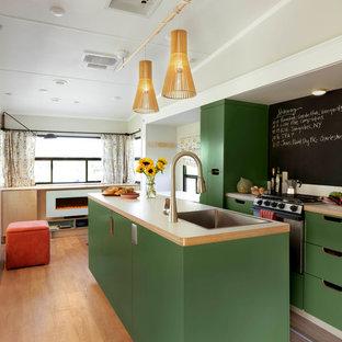 Immagine di una cucina ad ambiente unico moderna con lavello a vasca singola, ante lisce, ante verdi, elettrodomestici in acciaio inossidabile, pavimento in legno massello medio e isola