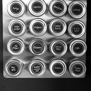 バーリントンの小さいエクレクティックスタイルのおしゃれなキッチン (シングルシンク、フラットパネル扉のキャビネット、淡色木目調キャビネット、ラミネートカウンター、黒いキッチンパネル、シルバーの調理設備の、淡色無垢フローリング) の写真