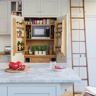 Inspiration for a traditional kitchen pantry in Surrey with shaker cabinets and an island.