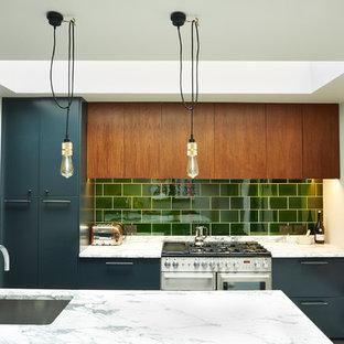 На фото: кухни в стиле фьюжн с врезной раковиной, плоскими фасадами, темными деревянными фасадами, зеленым фартуком, фартуком из плитки кабанчик, техникой из нержавеющей стали и островом