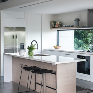 This is an example of a contemporary l-shaped kitchen in Gold Coast - Tweed with a single-bowl sink, flat-panel cabinets, white cabinets, window splashback, stainless steel appliances, concrete floors, with island, grey floor and white benchtop.