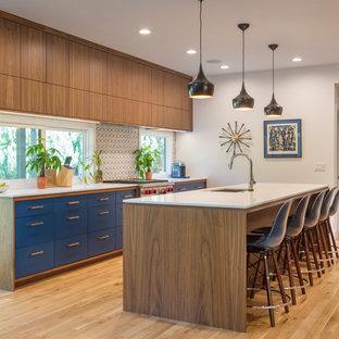 Mid-Century Küche mit Unterbauwaschbecken, flächenbündigen Schrankfronten, blauen Schränken, Rückwand-Fenster, Küchengeräten aus Edelstahl, hellem Holzboden und Kücheninsel in Kansas City