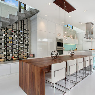 Trendy l-shaped eat-in kitchen photo in Orange County with flat-panel cabinets, white cabinets and stainless steel appliances