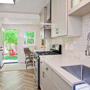 サンフランシスコの小さいインダストリアルスタイルのおしゃれなキッチン (アンダーカウンターシンク、シェーカースタイル扉のキャビネット、グレーのキャビネット、クオーツストーンカウンター、ベージュキッチンパネル、サブウェイタイルのキッチンパネル、シルバーの調理設備の、磁器タイルの床) の写真