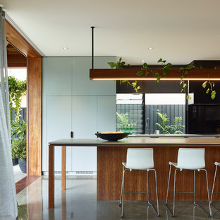 Photo of a contemporary galley kitchen in Brisbane with an undermount sink, flat-panel cabinets, medium wood cabinets, black splashback, concrete floors, with island, grey floor and grey benchtop.