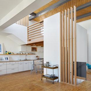 Foto de cocina lineal, industrial, abierta, con armarios con paneles lisos, puertas de armario blancas y suelo de contrachapado