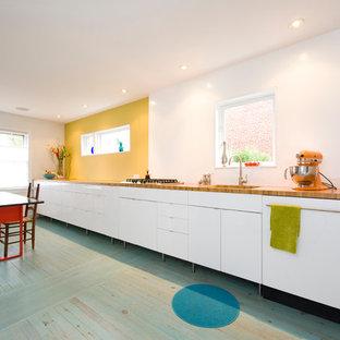 Пример оригинального дизайна интерьера: линейная кухня в скандинавском стиле с обеденным столом, плоскими фасадами, белыми фасадами, столешницей из дерева, деревянным полом и бирюзовым полом