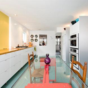 На фото: параллельная кухня в современном стиле с плоскими фасадами, обеденным столом, белыми фасадами, столешницей из дерева, белой техникой и бирюзовым полом с