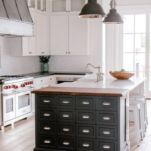 This is an example of a country l-shaped kitchen in Phoenix with a farmhouse sink, shaker cabinets, white cabinets, quartz benchtops, white splashback, stainless steel appliances, light hardwood floors and multiple islands.