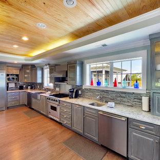 Ejemplo de cocina en L, costera, con fregadero bajoencimera, armarios con paneles con relieve, puertas de armario grises, salpicadero multicolor y electrodomésticos de acero inoxidable