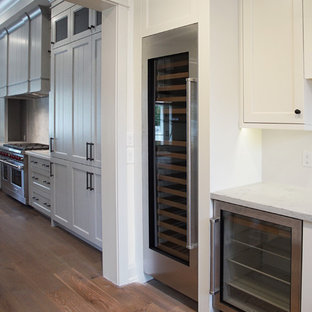Large traditional l-shaped eat-in kitchen in Phoenix with a farmhouse sink, louvered cabinets, grey cabinets, quartzite benchtops, white splashback, stone slab splashback, white appliances, dark hardwood floors, with island and brown floor.