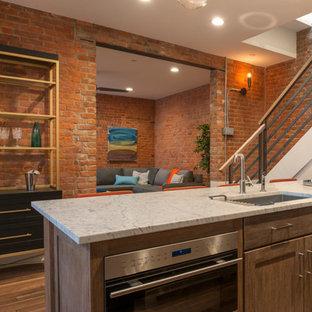 ブリッジポートの広いインダストリアルスタイルのおしゃれなキッチン (シングルシンク、シェーカースタイル扉のキャビネット、ベージュのキャビネット、クオーツストーンカウンター、レンガのキッチンパネル、シルバーの調理設備、淡色無垢フローリング、マルチカラーの床) の写真