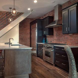 ブリッジポートの広いインダストリアルスタイルのおしゃれなキッチン (シングルシンク、シェーカースタイル扉のキャビネット、黒いキャビネット、クオーツストーンカウンター、セラミックタイルのキッチンパネル、シルバーの調理設備、淡色無垢フローリング、マルチカラーの床) の写真