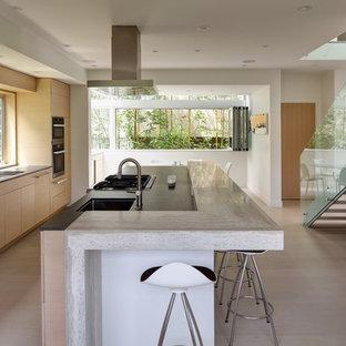 Einzeilige Skandinavische Wohnküche mit Unterbauwaschbecken, flächenbündigen Schrankfronten, hellen Holzschränken, Granit-Arbeitsplatte, hellem Holzboden, Kücheninsel, beigem Boden, schwarzer Arbeitsplatte und Rückwand-Fenster in Los Angeles