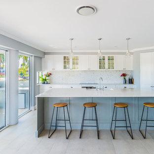 Cette image montre une cuisine marine avec un placard à porte vitrée, des portes de placard blanches, une crédence grise, un électroménager en acier inoxydable, un îlot central, un sol beige et un plan de travail gris.