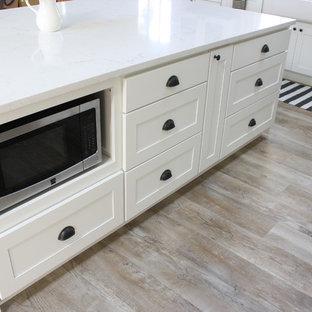 Lantlig inredning av ett stort kök, med en rustik diskho, skåp i shakerstil, vita skåp, bänkskiva i kvarts, vitt stänkskydd, stänkskydd i tunnelbanekakel, rostfria vitvaror, vinylgolv och en köksö