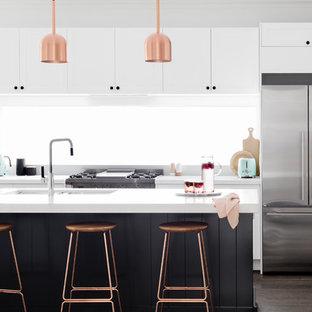 На фото: параллельные кухни-гостиные среднего размера в современном стиле с плоскими фасадами, техникой из нержавеющей стали, темным паркетным полом, врезной раковиной, белыми фасадами, фартуком с окном, островом и коричневым полом