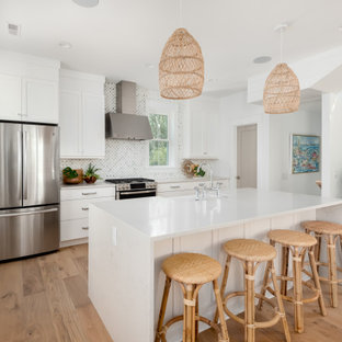 Large tropical open concept kitchen ideas - Example of a large island style single-wall light wood floor open concept kitchen design in Charleston with a farmhouse sink, shaker cabinets, white cabinets, quartz countertops, green backsplash, marble backsplash, stainless steel appliances, an island and white countertops