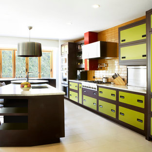 This is an example of an eclectic galley kitchen in San Francisco with green cabinets, yellow splashback and stainless steel appliances.