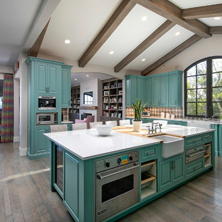 Inredning av ett medelhavsstil mycket stort vit vitt kök, med en rustik diskho, luckor med upphöjd panel, turkosa skåp, flerfärgad stänkskydd, rostfria vitvaror, mellanmörkt trägolv, en köksö och brunt golv