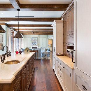 マイアミの中サイズの地中海スタイルのおしゃれなキッチン (アンダーカウンターシンク、落し込みパネル扉のキャビネット、淡色木目調キャビネット、人工大理石カウンター、茶色いキッチンパネル、木材のキッチンパネル、シルバーの調理設備の、無垢フローリング、茶色い床、ベージュのキッチンカウンター) の写真