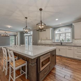 Idéer för ett stort klassiskt kök, med en enkel diskho, vita skåp, bänkskiva i kvartsit, grått stänkskydd, stänkskydd i stenkakel, integrerade vitvaror, en köksö, skåp i shakerstil, laminatgolv och brunt golv