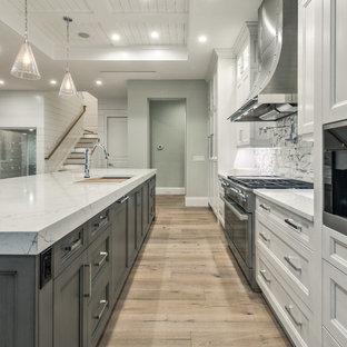 Offene, Große Moderne Küche in L-Form mit Unterbauwaschbecken, Schrankfronten mit vertiefter Füllung, grauen Schränken, Granit-Arbeitsplatte, Küchenrückwand in Beige, Rückwand aus Keramikfliesen, Küchengeräten aus Edelstahl, hellem Holzboden, Kücheninsel und braunem Boden in Miami