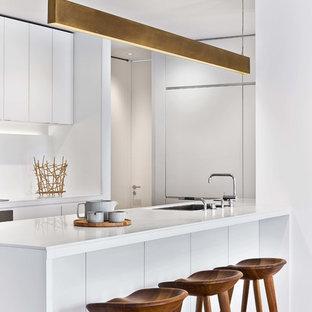 Ispirazione per una cucina ad U minimalista con lavello sottopiano, ante lisce, ante bianche, parquet chiaro, isola, pavimento beige e top bianco