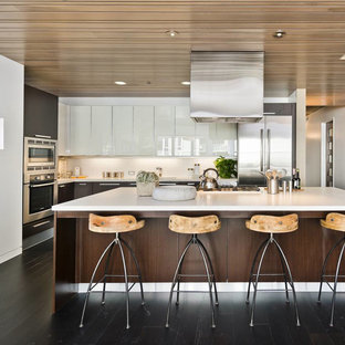 This is an example of a mid-sized contemporary l-shaped open plan kitchen in San Francisco with stainless steel appliances, an integrated sink, flat-panel cabinets, dark wood cabinets, quartz benchtops, white splashback, dark hardwood floors and with island.