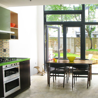 Example of a trendy kitchen design in London with stainless steel appliances, a drop-in sink, multicolored backsplash and green countertops