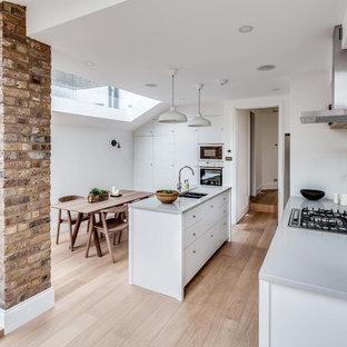 Ispirazione per una cucina nordica con lavello sottopiano, ante lisce, ante bianche, paraspruzzi a specchio, parquet chiaro e isola