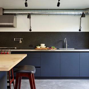 Industrial Küche mit integriertem Waschbecken, flächenbündigen Schrankfronten, schwarzen Schränken, Edelstahl-Arbeitsplatte, Küchenrückwand in Schwarz, Küchengeräten aus Edelstahl, Betonboden, Kücheninsel, grauem Boden und grauer Arbeitsplatte in London