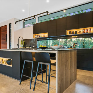 Photo of a contemporary galley open plan kitchen in Sunshine Coast with flat-panel cabinets, black cabinets, window splashback, panelled appliances, concrete floors, with island, beige floor and black benchtop.