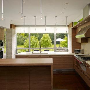 Idée de décoration pour une grand cuisine américaine design en U avec un évier encastré, des portes de placard en bois brun, une crédence beige, un électroménager en acier inoxydable, un îlot central, un placard à porte plane, un sol en vinyl et un sol marron.