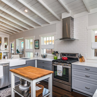 Traditional open concept kitchen designs - Inspiration for a timeless u-shaped dark wood floor open concept kitchen remodel in Tampa with a farmhouse sink, raised-panel cabinets, gray cabinets, white backsplash, subway tile backsplash, stainless steel appliances and an island