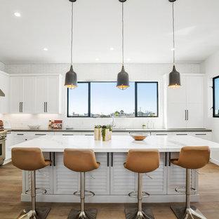 Immagine di una cucina ad ambiente unico classica con lavello sottopiano, ante a persiana, ante bianche, paraspruzzi bianco, paraspruzzi con piastrelle diamantate, elettrodomestici in acciaio inossidabile, pavimento in legno massello medio, isola, pavimento marrone e top bianco