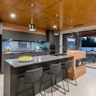 Design ideas for a large contemporary galley open plan kitchen in Canberra - Queanbeyan with flat-panel cabinets, black cabinets, glass sheet splashback, black appliances, light hardwood floors, with island, white floor and grey benchtop.