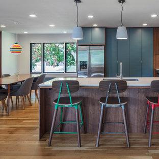 Immagine di una cucina abitabile minimalista di medie dimensioni con lavello sottopiano, ante lisce, ante blu, top in quarzo composito, paraspruzzi bianco, paraspruzzi con piastrelle in ceramica, elettrodomestici in acciaio inossidabile, parquet chiaro e penisola