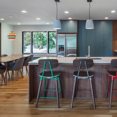 Mid-sized mid-century modern light wood floor eat-in kitchen photo in Kansas City with an undermount sink, flat-panel cabinets, blue cabinets, quartz countertops, white backsplash, ceramic backsplash, stainless steel appliances and a peninsula