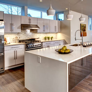 Mid-sized trendy galley medium tone wood floor open concept kitchen photo in Seattle with an undermount sink, flat-panel cabinets, white cabinets, multicolored backsplash, stainless steel appliances and an island