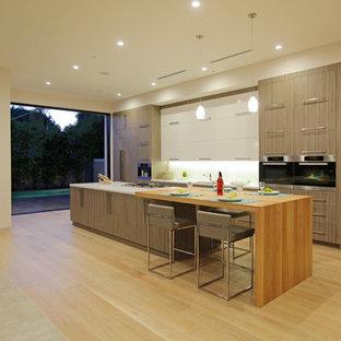 ロサンゼルスのコンテンポラリースタイルのおしゃれなキッチン (アンダーカウンターシンク、フラットパネル扉のキャビネット、中間色木目調キャビネット、木材カウンター、白いキッチンパネル、ガラス板のキッチンパネル、シルバーの調理設備) の写真